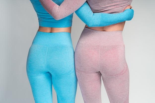 Photo recadrée de deux sportives méconnaissables avec de longues jambes minces vêtues de vêtements de sport se tenant dos à la caméra tout en posant à l'intérieur contre un mur blanc