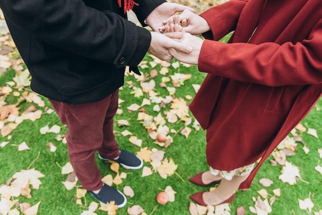Photo recadrée du couple homme et femme se tenant la main au rendez-vous romantique. aime le style de vie en plein air avec la nature en arrière-plan