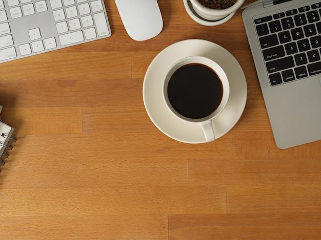 Photo recadrée d'employé de bureau travaillant avec tablette numérique et papeterie sur table en bois