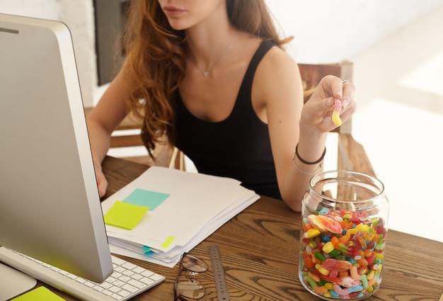 Photo recadrée de l'employée de bureau caucasienne prenant la marmelade du grand pot au travail. la jeune fille mange des bonbons pour l'amélioration du travail du cerveau pendant un travail acharné sur les états financiers