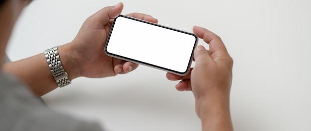 Photo recadrée d'un entrepreneur masculin tenant un smartphone horizontal