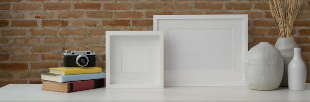 Photo recadrée d'un espace de travail contemporain avec des cadres, des vases en céramique, un appareil photo et des livres