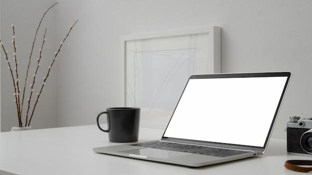 Photo recadrée de l'espace de travail avec un ordinateur portable à écran blanc, une tasse de café, un cadre et un appareil photo sur un bureau avec un mur blanc