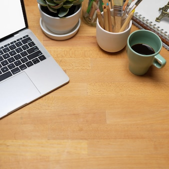 Photo recadrée de l'espace de travail avec ordinateur portable, tasse à café, fournitures et espace de copie dans la salle de bureau à domicile