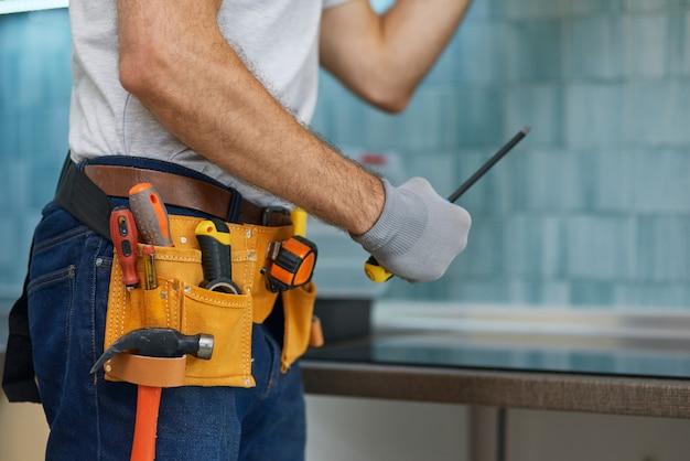 Photo recadrée d'experts d'un jeune plombier professionnel réparateur tenant un tournevis tout en réparant un