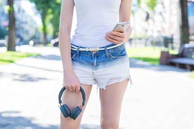 Photo recadrée à faible angle de vue rapprochée d'une jolie jolie fille séduisante charmante tenant un téléphone intelligent utilisant un casque à la main et gris choisissant la chanson préférée