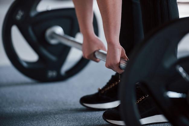 Photo recadrée d'une femme accroupie avec haltères dans la salle de sport