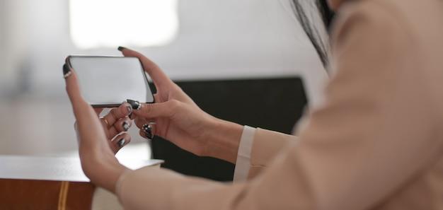 Photo recadrée de femme d'affaires à l'aide d'une maquette de smartphone tout en travaillant sur son projet dans une salle de bureau confortable