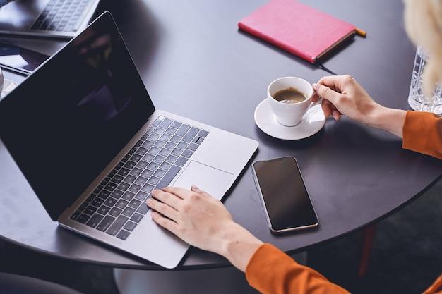 Photo recadrée d'une femme d'affaires blonde assise avec une tasse d'espresso à table