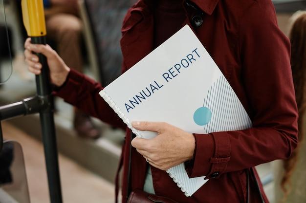 Photo recadrée d'une femme d'affaires méconnaissable tenant des documents dans un bus lors d'un voyage en transports en commun en ville, espace de copie