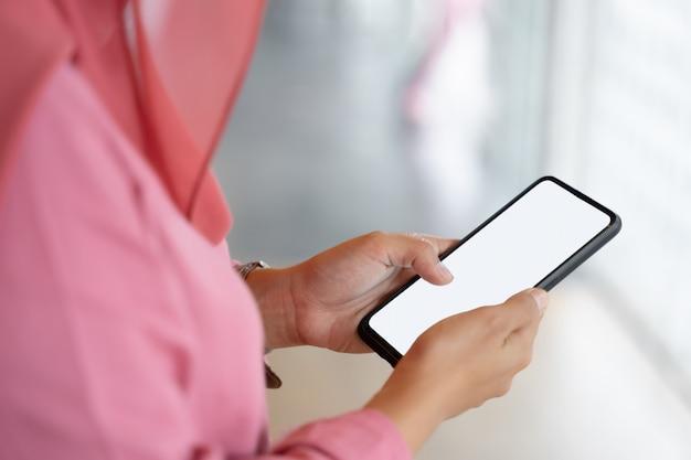 Photo recadrée de femme d'affaires musulmanes en hijab rose et vêtements décontractés debout et à l'aide de smartphone.