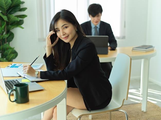 Photo recadrée de femme d'affaires souriant tout en travaillant avec la paperasse d'affaires dans la salle de bureau avec un collègue