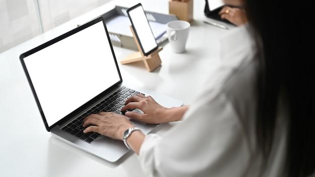 Photo recadrée d'une femme d'affaires travaillant sur un ordinateur portable et un téléphone intelligent avec écran blanc dans un bureau moderne.