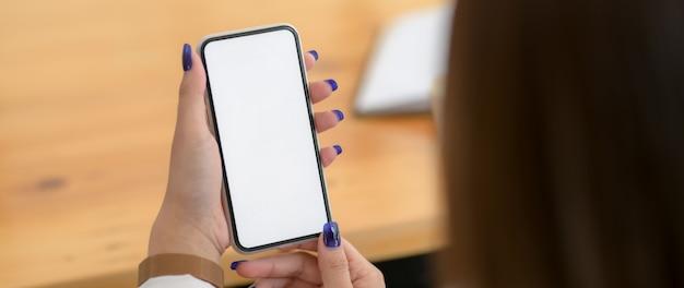 Photo recadrée de femme à l'aide de smartphone sur un bureau en bois
