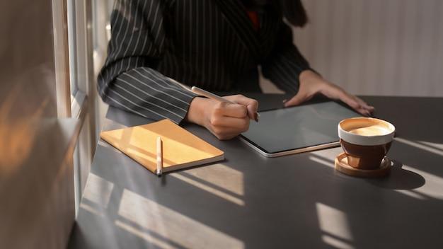 Photo recadrée de femme à l'aide d'une tablette numérique dans un lieu de travail confortable