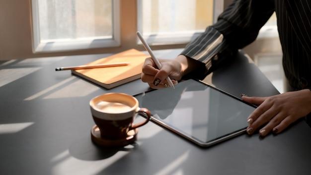 Photo recadrée de femme à l'aide de tablette numérique dans un lieu de travail moderne sombre
