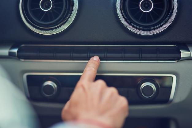 Photo recadrée d'une femme appuyant sur le bouton du tableau de bord de la voiture en conduisant en ville en gros plan