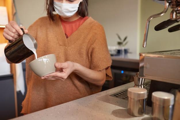 Photo recadrée d'une femme barista créant de l'art latte avec de la crème tout en préparant du café frais dans un café ou un café, espace de copie