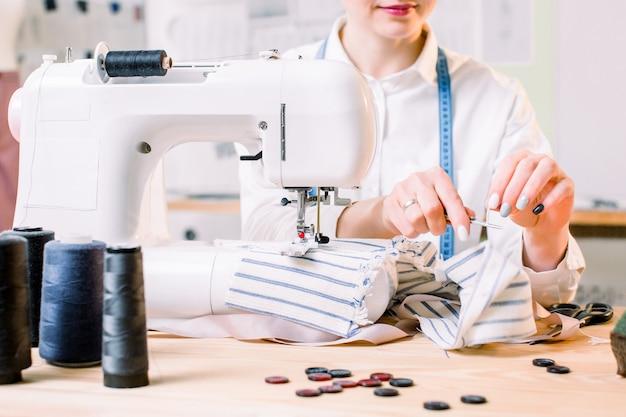 Photo recadrée de femme cousant sur machine en studio de design. jeune couturière coud des vêtements. lieu de travail du tailleur - machine à coudre, rouleaux de fil, tissu, ciseaux. focus sur la machine à coudre