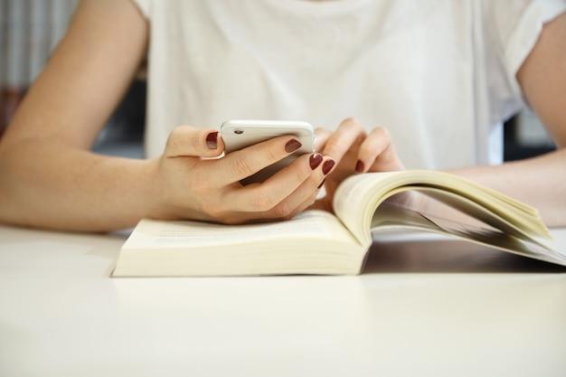 Photo recadrée d'une femme avec une manucure soignée portant un chemisier blanc avec ses mains sur un livre ouvert, naviguant sur internet à l'aide d'un téléphone portable tout en étudiant et en recherchant des informations à la bibliothèque