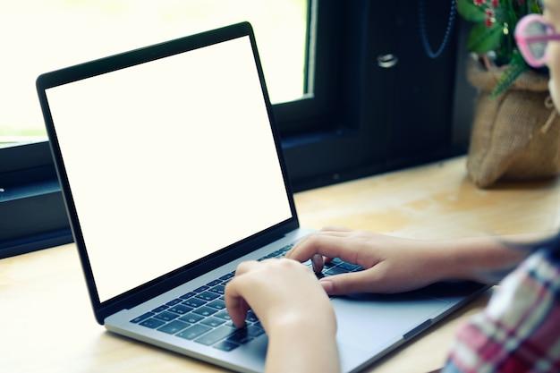 Photo recadrée d'une femme méconnaissable travaillant sur son ordinateur portable à la maison.