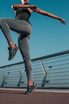 Photo recadrée d'une femme mettant une jambe en l'air et étirant ses bras