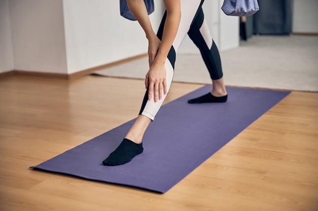 Photo recadrée d'une femme mince étirant son corps sur un tapis de gymnastique spécial dans un studio de fitness