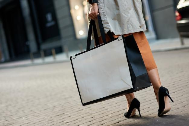 Photo recadrée d'une femme portant des chaussures à talons hauts portant un gros sac à provisions marchant dans les rues de la ville