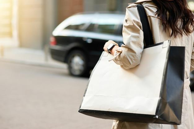 Photo recadrée d'une femme portant un gros sac à provisions marchant dans les rues de la ville
