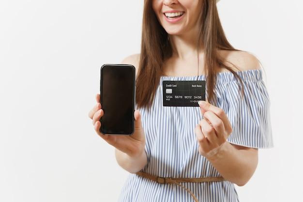 Photo recadrée d'une femme en robe bleue montrant un téléphone portable avec appareil photo avec un écran vide noir vierge, tenant une carte de crédit isolée sur fond blanc. personnes, concept bancaire. espace publicitaire. espace de copie.