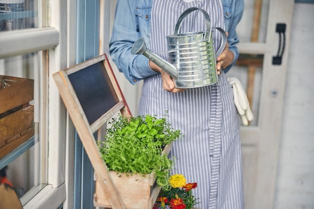 Photo recadrée d'une femme en tablier debout avec un arrosoir dans les mains