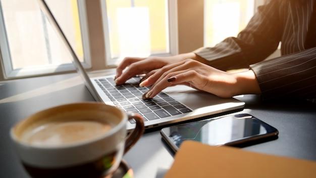 Photo recadrée de femme tapant sur un ordinateur portable sur un tableau noir dans un lieu de travail confortable