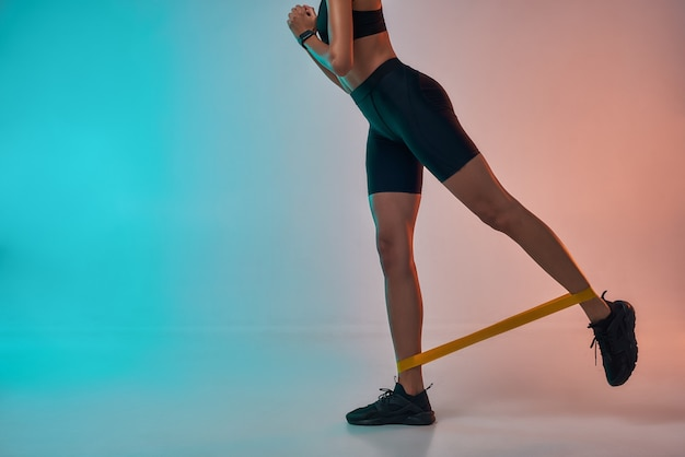 Photo recadrée de fesses parfaites d'une femme athlète en vêtements de sport faisant de l'exercice avec une bande de résistance