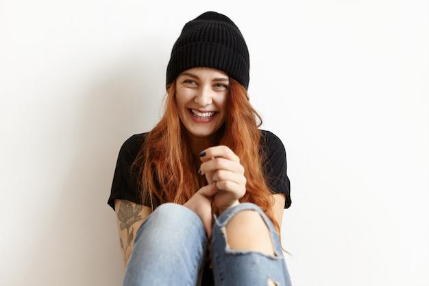 Photo recadrée d'une fille heureuse avec des cheveux roux lâche portant un chapeau noir élégant, un t-shirt et un jean bleu déchiqueté