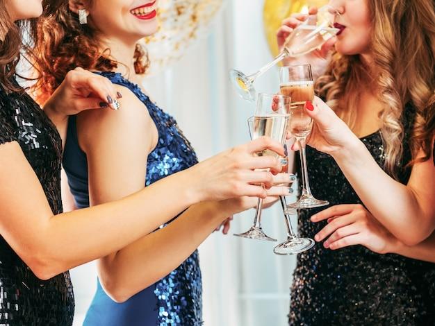 Photo recadrée de filles tintant des verres de champagne, buvant des toasts pour l'anniversaire de leur ami.