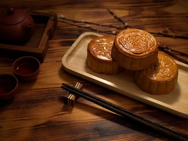 Photo recadrée de gâteaux de lune traditionnels sur plaque en bois. le caractère chinois sur le gâteau de lune représente