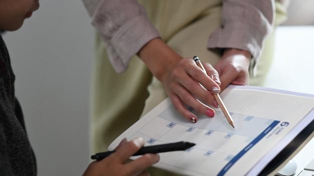 Photo recadrée de gens d'affaires tenant un calendrier pour planifier des rendez-vous. concept de gestion de l'organisation du planificateur de calendrier.