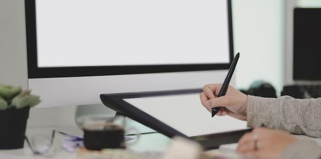 Photo recadrée de graphiste dessinant son projet sur tablette numérique