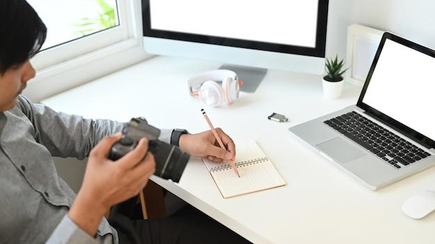 Une photo recadrée d'un graphiste ou d'un photographe vérifie les aperçus sur la caméra dans le studio.