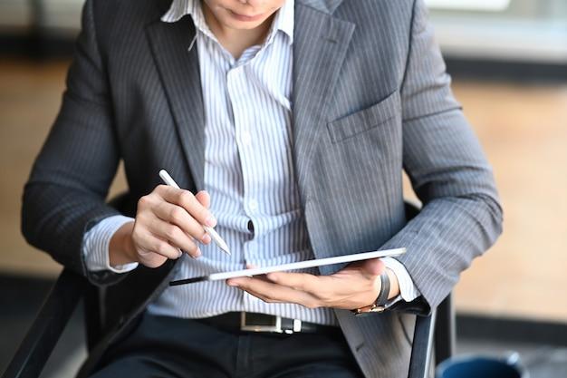 Photo recadrée d'un homme d'affaires assis sur une chaise confortable et utilisant un téléphone intelligent.