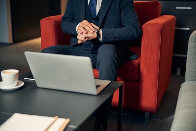 Photo recadrée d'un homme d'affaires assis dans le fauteuil du salon et touchant la montre à son poignet. tasse de café et un ordinateur portable sur la table