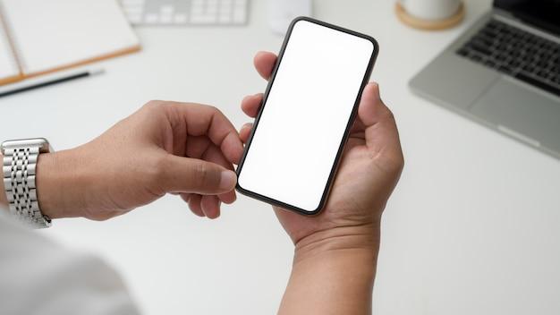 Photo recadrée d'homme d'affaires détenant un smartphone à écran blanc sur un bureau blanc