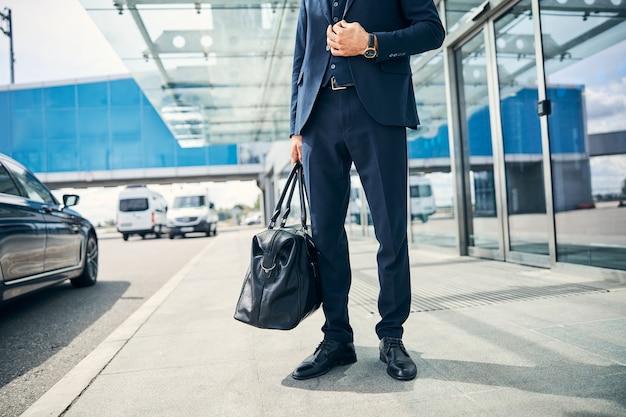 Photo recadrée d'un homme d'affaires tenant ses bagages et touchant son blazer alors qu'il se tenait devant un terminal d'aéroport