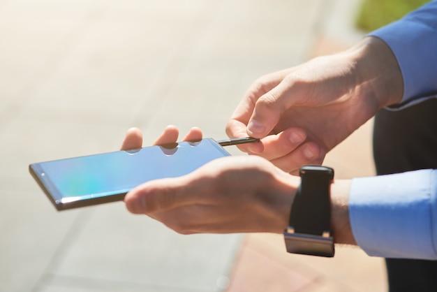 Photo recadrée d'un homme d'affaires utilisant une clé usb pour smartphone tout en travaillant à l'extérieur sous le soleil