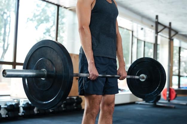 Photo recadrée d'un homme athlétique. avec haltères