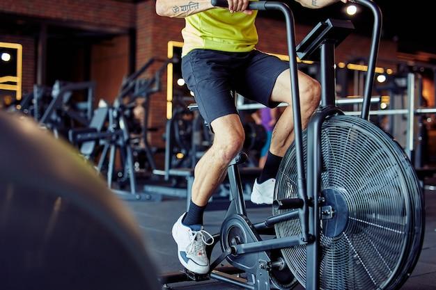 Photo recadrée d'un homme athlétique en tenue de sport faisant du vélo sur des vélos d'exercice au gymnase d'entraînement cardio