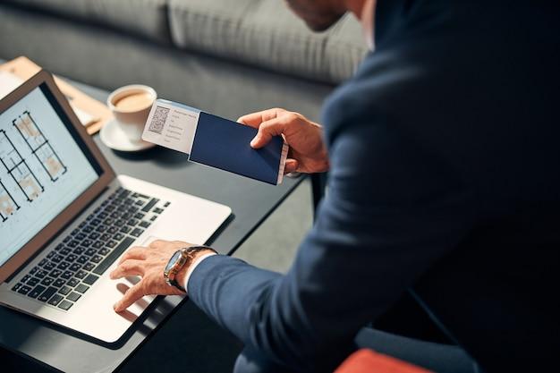 Photo recadrée d'un homme en costume assis devant un écran d'ordinateur portable tout en tenant un passeport avec son billet d'avion