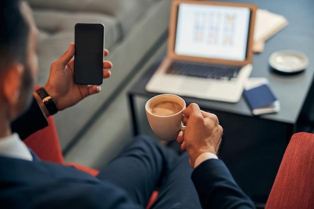 Photo recadrée d'un homme en costume assis avec une tasse de café et un ordinateur portable en arrière-plan et tenant un téléphone portable moderne