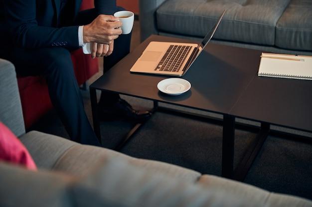 Photo recadrée d'un homme en costume tenant une tasse de café assis devant un ordinateur portable dans un salon d'affaires
