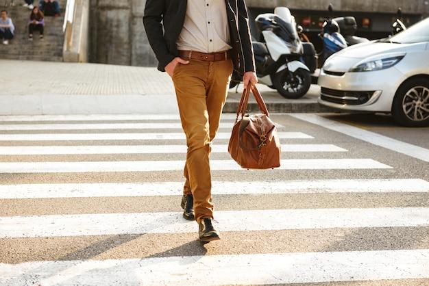 Photo recadrée d'un homme élégant et prospère dans des vêtements d'affaires marchant à travers un passage pour piétons au centre-ville, avec un sac en cuir pour homme à la main
